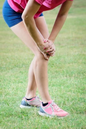 Female athlete suffer because an injury in her knee  Stock Photo