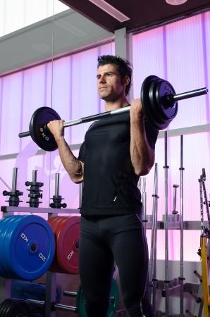 levantamiento de pesas: Hombre duro entrenamiento del b�ceps en el fondo gimnasio y pesas