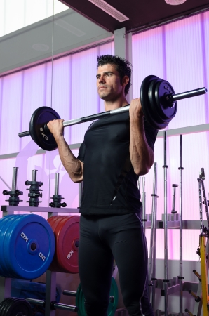weightlifting equipment: Man training biceps hard on gym background and weights  Stock Photo