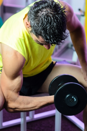 Training biceps with dumbbell in gym. photo