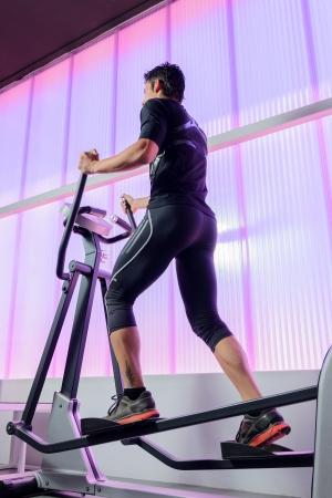 eliptica: El hombre nuevo, entrenamiento cardiovascular en la elíptica en el gimnasio. Foto de archivo