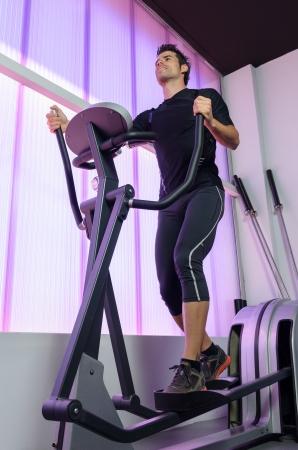 perspire: Man training hearth with cardio exercising in elliptical machine.