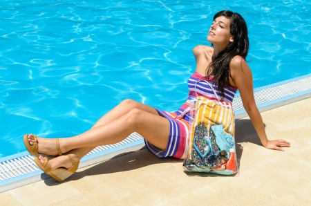 Young woman with colorful dress lying, sunbathing and laughing at poolside on blue water background  Hot summer day