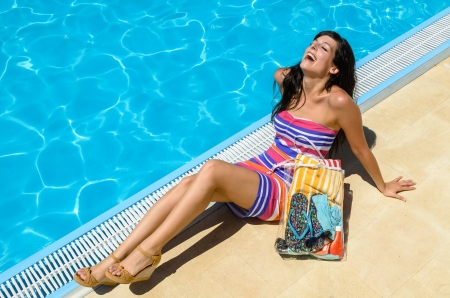 Young woman with colorful dress lying, sunbathing and laughing at poolside on blue water background  Hot summer day  photo