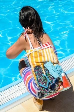 en cuclillas: Verano concepto con una mujer irreconocible en cuclillas para tocar el agua azul en la piscina en los días de calor Foto de archivo