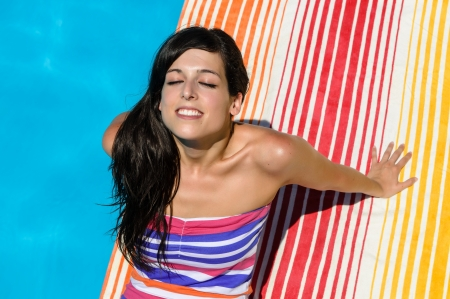 Young woman with colorful dress sunbathing and smiling at poolside on blue water background. Hot summer day. Stock Photo - 14525808