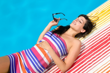Young woman with colorful dress and sunglasses lying and sunbathing at poolside on blue water background in a hot summer day. Stock Photo - 14525805