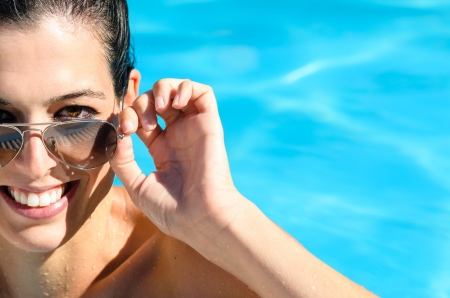 Woman with beautiful smile enjoys summer in pool. photo