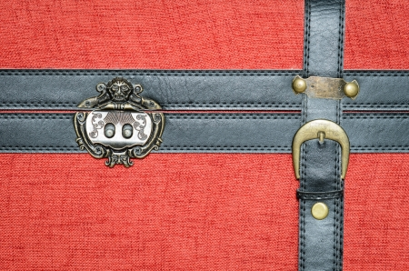 Closure of an old trunk, covered with red fabric, with black leather straps and metal buckle gold. Stock Photo