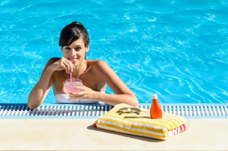Woman drinking soda while enjoys the summer heat  in a cool blue water swimming pool  In front of her a colorful towel, suntan lotion and sunglasses  photo