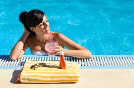 Woman with glass of soda close her eyes while enjoys the summer  in a blue water swimming pool  In front of her a colorful towel, suntan lotion and sunglasses  photo