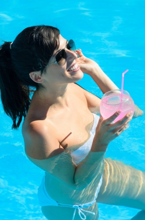 Woman smiling and drinking a cocktail in swimming pool a hot summer day  She wears white bikini and sunglasses  photo