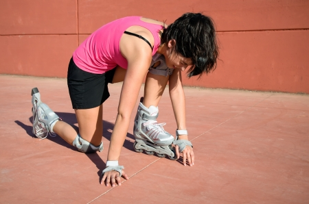Female roller skater accident over hard asphalt  She wears protections and sport wear and shows face of suffering Stock Photo - 14889922