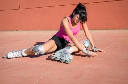 rollerblading: Mujer accidente patinador rodillo sobre asfalto duro Lleva protecciones y ropa de deporte y muestra el rostro del sufrimiento Foto de archivo
