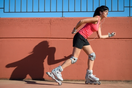 Woman skates in front of a wall casting shadow in a hot summer day. She wears protections for knee and wrist. photo