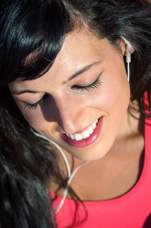 Young woman in sport wear enjoys and smiles listening music with white earphones. Stock Photo - 14889936
