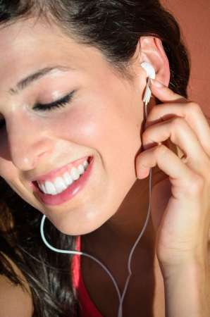 Young woman in sport wear enjoys and smiles listening music with white earphones. she presses the headset on the ear with a finger. Stock Photo - 14889959