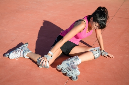 Female roller skater with protections falls by accident. She suffer an injury, grabs her knee and shows face of pain.