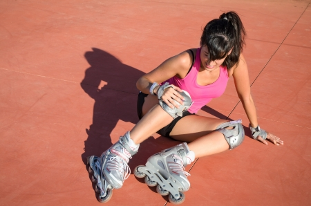 inline skates: Female roller skater with protections falls by accident. She suffer an injury, grabs her knee and shows face of pain. Stock Photo