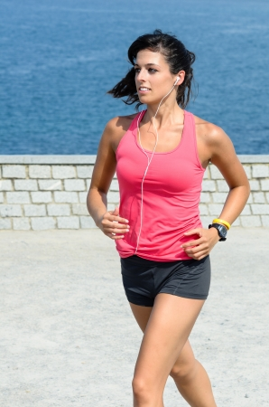 Sport woman running with sea at background. She is smiling and  wears earphones. photo