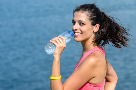 Woman looking at camera and drinking water from bottle. She is smiling. Blue sea at the background. photo