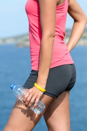 hand water: Detail of womans arm and hand holding a bottle of water in front of the sea and coast. Healthy lifestyle concept. Stock Photo