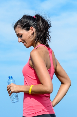 sportwoman: Sport woman smiling, holding and looking at a bottle of water on sky background