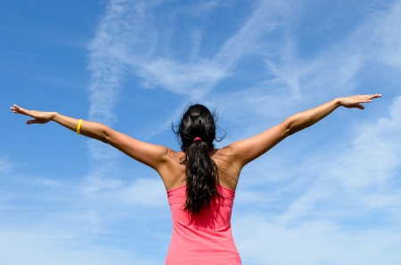raised: Girl from behind with arms raised like wings towards sky on a sunny summer day.