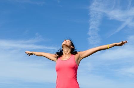 dia soleado: Ni�a feliz con los brazos levantados hacia el cielo azul en un d�a soleado de verano.