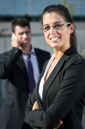 Cheerful business woman with glasses standing while business man is talking by phone on background photo