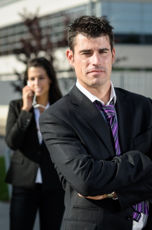 Handsome business man idly and looking at camera while bussineswoman is talking by phone on background photo