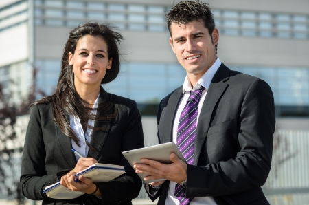 dictating: Business man and woman smiling and taking notes in tablet and notebook outdoors Stock Photo
