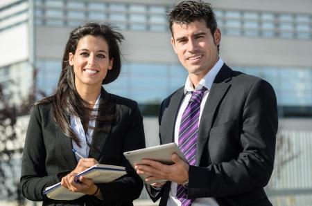 dictating: Hombre y mujer de negocios sonriendo y tomando notas en tabletas y port�tiles al aire libre