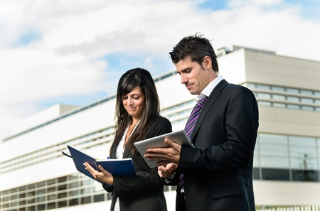 two companies: Cheerful business people taking notes in front of company building Stock Photo