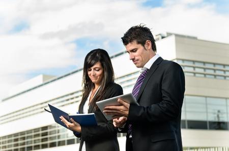 dictating: Gente alegre de negocios tomando notas en frente del edificio de la empresa