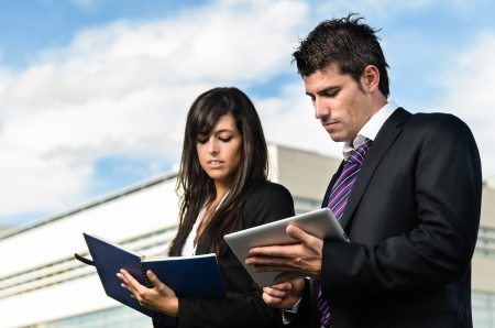 Business people taking notes in front of company building Stock Photo - 15037983