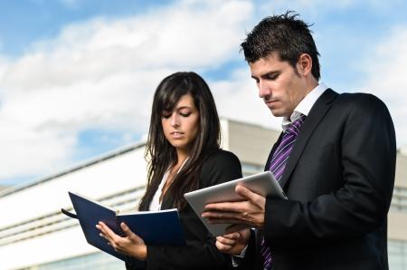 dictating: La gente de negocios tomando notas en frente del edificio de la empresa