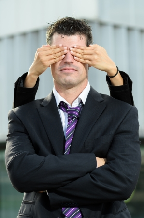 guess: Female hands covering the eyes of handsome business man Stock Photo