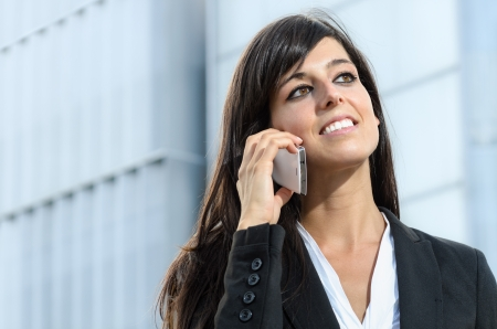 Businesswoman smiling and talking by phone on blur background photo