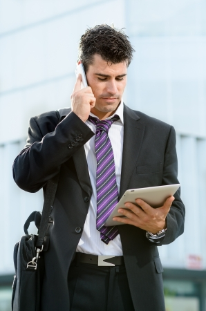 corporate responsibility: Handsome business man looking diary on tablet while talking by phone