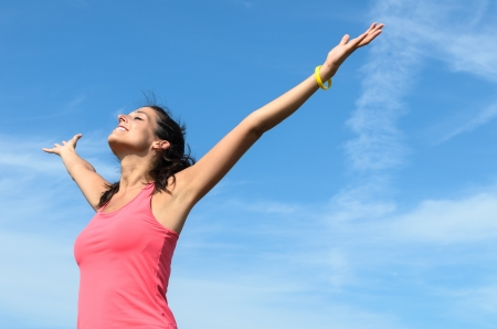 toward: Cheerful woman raising arms toward the sky showing her happiness