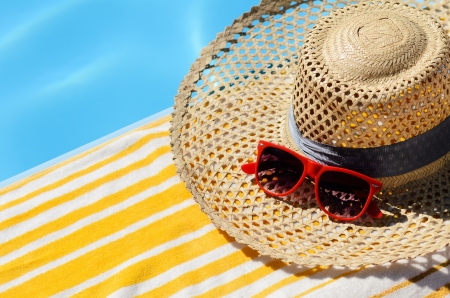 Summer concept. Yellow towel, red sunglasses and straw hat on blue water background