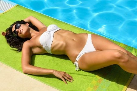 Tanned young brunette woman with bikini and sunglasses at poolside sunbathing and relaxing