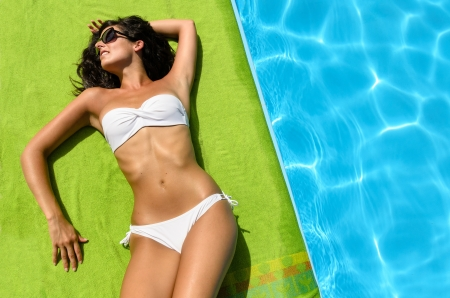 Tanned young brunette woman with bikini and sunglasses at poolside sunbathing and relaxing photo