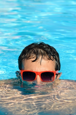 above head: Young man diving into a pool with red sunglasses. He takes half a head above the water Stock Photo