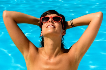 Young brunette woman enjoying the sun in a swimming pool, with hands on head looking at the sun. Stock Photo - 15264866
