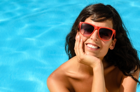 Beautiful brunette looking cheerful at camera in a pool on blue water background Stock Photo - 15264868