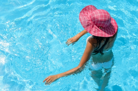 pink hat: Brunette woman enjoys summer and water in swimming pool Stock Photo