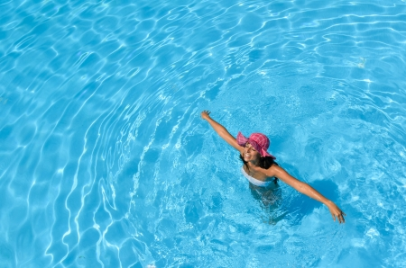 Brunette woman smiling with arms raised,  enjoying summer and water in swimming pool photo