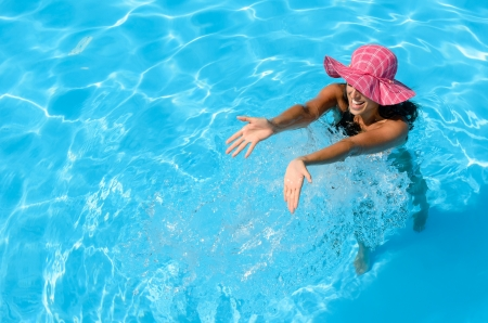 Brunette woman splashing water and having fun in swimming pool Stock Photo - 15370111